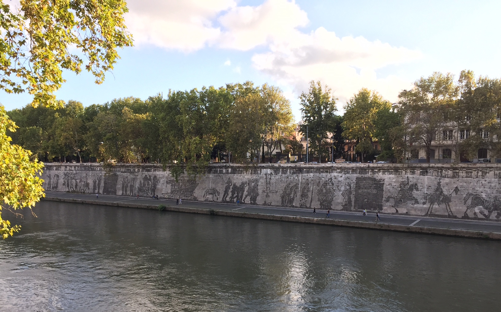 View of 'Triumps and Laments' from across the Tiber with ant-like figures in front of the frieze to show the colossal scale