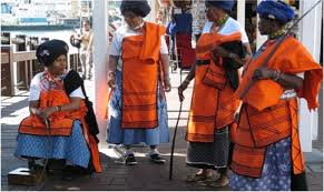Xhosa women wearing traditional orange blankets over shwe-shwe dresses Source: Pinterest MeerkatShweshwe.com