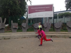 Two kids run to catch up with their friends with Vilakazi spelt out in sign language in the background Source:
