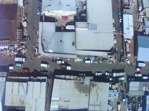 Aerial View Kliptown June 2004 showing street traders, houses. Union Street runs horizontally across the image. Source: JDA